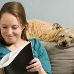 Woman reading with dog